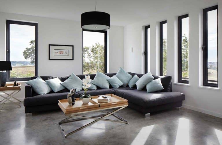 Comfortable corner group sofa in bright living room with aluminium windows.